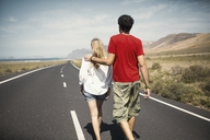 Rear view of couple with arm around walking on road - FSIF01599