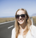 Smiling young woman wearing sunglasses on road - FSIF01602