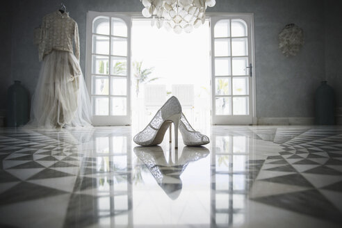 High heels and wedding dress in front of open door - FSIF01626