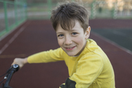 Portrait of smiling boy cycling in court - FSIF01635