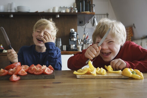 Happy brothers holding knives at table with vegetables in kitchen - FSIF01641