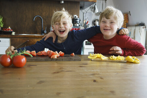 Portrait of happy brothers sitting at table with vegetables in kitchen - FSIF01647
