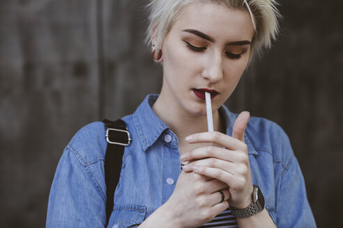 Young fashionable woman smoking cigarette while standing outdoors - FSIF01674