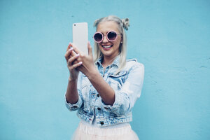 Happy fashionable young woman talking selfie against blue wall - FSIF01680