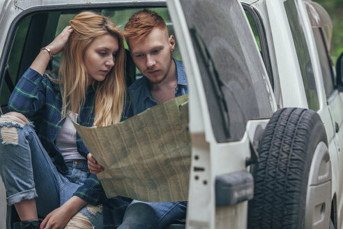 Couple analyzing map while sitting in off-road vehicle at forest - FSIF01695