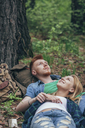 Romantic couple lying on field at forest - FSIF01698