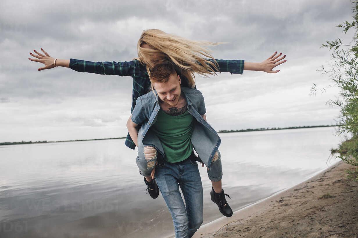 Happy man piggybacking girlfriend on lakeshore against sky - FSIF01701 - fStop/Westend61
