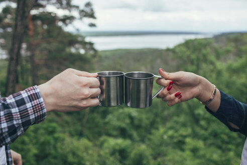 Cropped image of man and woman toasting steel mugs against forest - FSIF01704