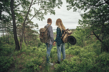 Rear view of couple holding hands while hiking at forest - FSIF01710