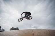 Low angle view of teenager performing stunt during BMX cycling against cloudy sky - FSIF01731