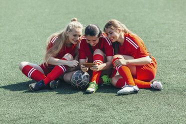 Cheerful soccer players using smart phone while sitting on field - FSIF01740