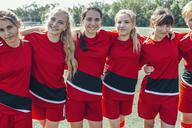 Portrait of smiling soccer team standing on field - FSIF01743