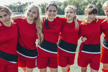 Portrait of smiling soccer team standing on field - FSIF01743