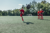 Soccer player kicking ball while friends stand nearby on field - FSIF01746
