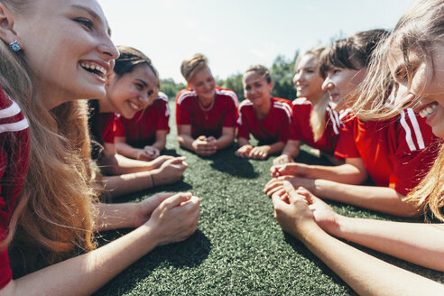 Close-up of sports team lying on playing field - FSIF01752