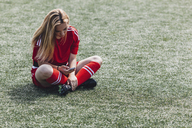 Soccer player using smart phone while sitting on field - FSIF01755