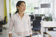 Confident thoughtful businesswoman standing at creative office - FSIF01770