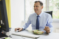 Smiling businessman working on computer while having salad at desk in creative office - FSIF01782