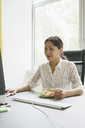 Businesswoman using computer while having salad at office desk - FSIF01794
