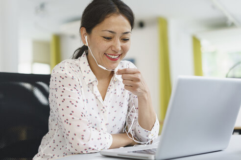 Smiling businesswoman using headphones and laptop at office desk - FSIF01797