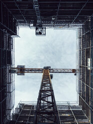 Directly below shot of crane amidst glass building against sky - FSIF01803