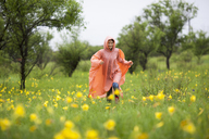 Woman wearing raincoat running amidst yellow flowering plants in rainy season - FSIF01818