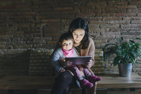 Mother and daughter using digital tablet at home - GEMF01883