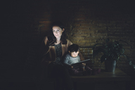 Mother and daughter using cell phone and digital tablet at home in the dark - GEMF01886