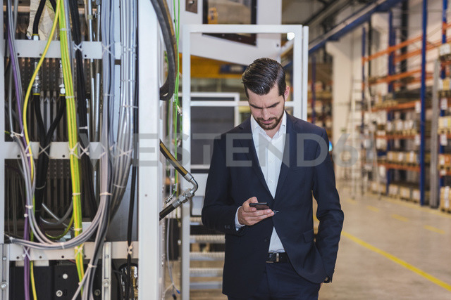Businessman in factory checking cell phone - DIGF03388