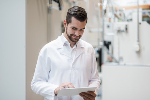 Man wearing lab coat in factory using tablet - DIGF03391