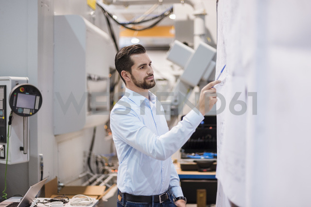 Businessman in factory looking at plan - DIGF03400