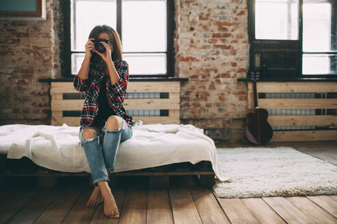 Full length of woman photographing through SLR camera in bedroom at home - FSIF01842