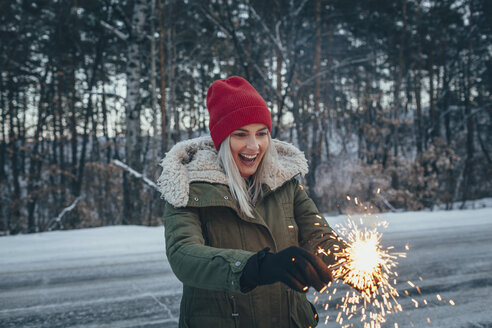 Happy woman holding sparklers while standing on field during winter - FSIF01854