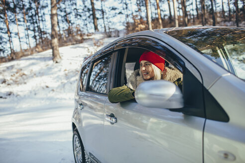 Happy young woman in car during winter - FSIF01857