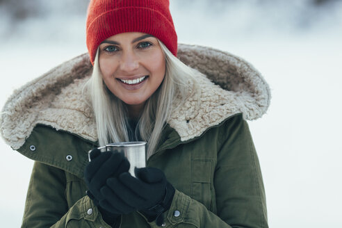 Portrait of young woman having coffee during winter - FSIF01872