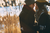 Young couple embracing while standing on field during winter - FSIF01875