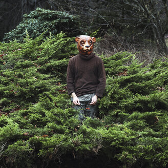 Man wearing bear mask while standing amidst plants - FSIF01881