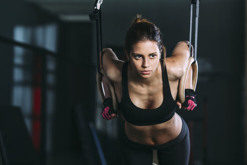Front view of woman hanging on gymnastic rings at gym - FSIF01944