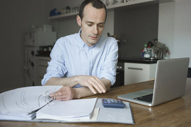 Serious man working with laptop and file at home - FSIF01959