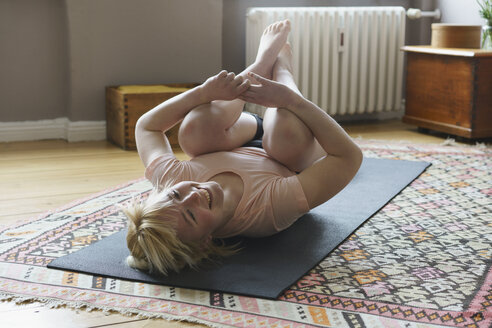 Happy woman exercising on mat in living room - FSIF01971
