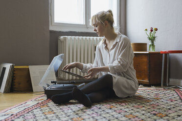 Full length of woman playing record while sitting at home - FSIF01974