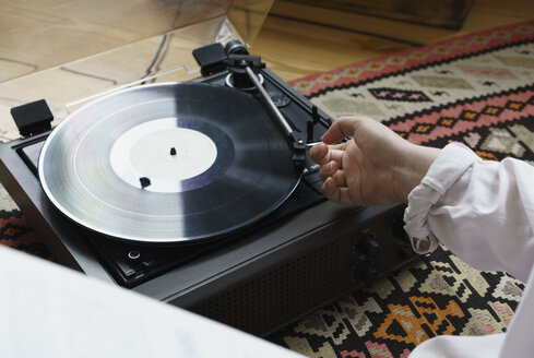 Cropped image of woman playing record at home - FSIF01977