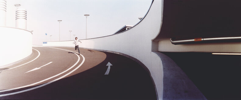 Man running on empty highway - FSIF02043