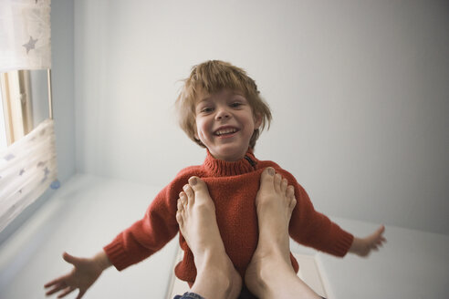 Young boy balancing on adult feet - FSIF02127