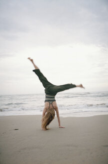Young woman doing cartwheel on beach - FSIF02154