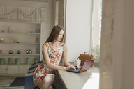 Young woman using laptop while sitting by window at cafe - FSIF02172