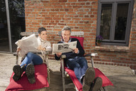 Mature couple reading newspaper while sitting in back yard - FSIF02205