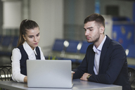Young businessman and businesswoman using laptop at airport - FSIF02223