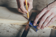 Cropped hands of carpenter marking on plank with pencil and ruler at workshop - FSIF02244