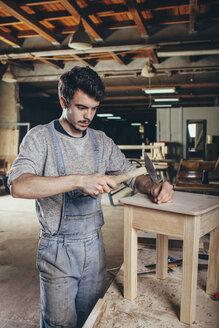 Carpenter hammering nail into wooden stool at workshop - FSIF02259